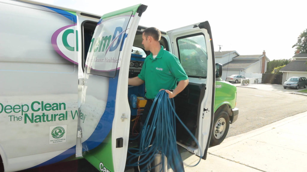 carpet cleaning technician getting tools from a van